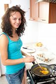 image of scrambled eggs  - young attractive female prepares scrambled egg for breakfast - JPG