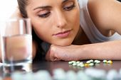 stressed attractive young brunette with some pills and glass of water