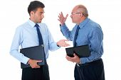 young and older businessman have argument over their work, one of them hold small computer, isolated