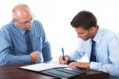 senior and junior businessman discuss and argue over something during their meeting, younger one sign contract or some documents, isolated on white