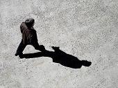 Homem andando na calçada com sombra preta