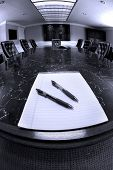Conference room table with several leather chairs and notebook with pens