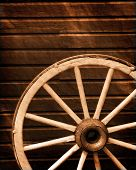 picture of wagon wheel  - Antique wagon wheel leaning against old wooden wall - JPG