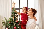 family, winter holidays and people concept - happy mother and little daughter decorating christmas t poster