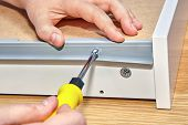 Installation Furniture, Screwing Screw-bolt With Using Hand Screwdriver, Close-up. poster