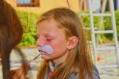 Woman Painting Face Of Kid Outdoors. Baby Face Painting. Little Girl Getting Her Face Painted Like A poster