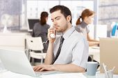 Young office worker sitting at desk in office, talking on phone, using laptop, women working in the