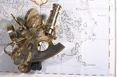 A small sextant on a 100-year-old map showing shoals and sandbanks close to shore. Symbolising dealing with hazards