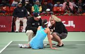 Serbian tennis star Ana Ivanovicgets assistance from WTA officials after twisting her ankle at the Q