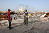 Asian fishermen preparing their fish traps at the Dhow Harbour in Doha, Qatar, April 2008. The new I