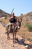 WHITE MOUNTAINS, CRETE - JULY 2008:  A peasant farmer on his donkey on the road between Kali Sykia a