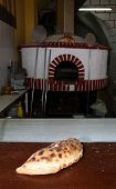 A calzone pizza on a baker's table with a traditional Mediterranean wood fired oven (sometimes calle