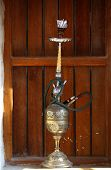 An old hookah or shisha pipe with a brass bowl on a window-cill with a wooden shutter behind, in Sou