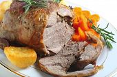 A serving plate with a joint of roasted boneless lamb roasted potatoes and boiled carrots, garnished