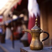 A coffee pot - the Arab symbol of welcome - in front of a Qatari flag in Souq Waqif, Doha, Qatar. Th