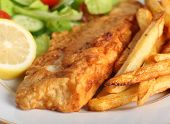 A piece of fish in batter served with french fried potato chips, lemon and a lettuce, rocket, cucumb