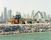DOHA, QATAR - APRIL 26: Heavy construction machinery at work on harbour alterations  with the city's high-rise skyline behind, in Doha Bay,in Doha, Qatar on April 26 2011. Qatar is hotspot for construction activity.