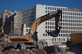 picture of urbanisation  - Excavator on construction  site dismatling old buildings