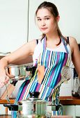 Young Housewife On Domestic Kitchen poster