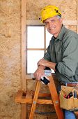 Closeup of  a carpenter leaning on a ladder in front of a wall he is building. Vertical Format.