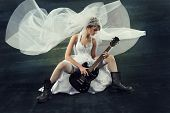 Bride Playing Rock Guitar Over Artistic Dark Background