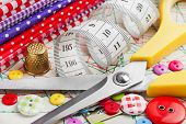 Sewing Items: Buttons, Colorful Fabrics, Scissors, Measuring Tape, Thimble, Spools Of Thread On Sewi