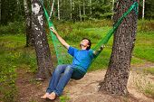 Barefooted man sits in hammock suspended between two thik birches, head thrown back, eyes closed