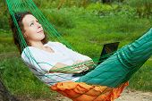 Young woman looks at the sky, lying in hammock, notebook lies on her stomach