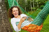 Young smiling woman lies in hammock with tablet PC outdoors at birchwood