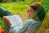 Young woman lies in hammock and reads book