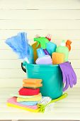 Cleaning items in bucket on  white wooden background