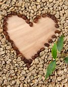 Green and brown coffee beans with leaves on wooden background