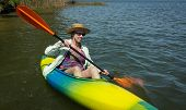 Mature Woman Enjoys Peaceful Paddling In Her Kayak