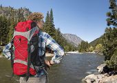 Hiker, with backpack, standing on the banks of the Wenatchee River, near Leavenworth in the Cascade