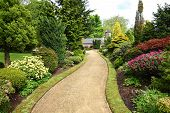 stock photo of conifers  - Beautiful spring garden design with blooming flowers and a path - JPG