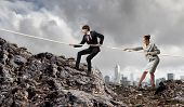 Image of busionessman and businesswoman pulling rope atop of mountain