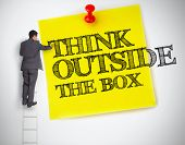 stock photo of thinking outside box  - Businessman writing think outside the box on a giant post it helped by a ladder - JPG