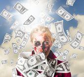 stock photo of scrooge  - Rich zombie outdoors in the sun looking shocked with a ton of falling money - JPG