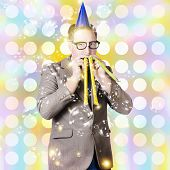 stock photo of dorky  - Creative portrait of a dorky new years eve man blowing celebration horns at a countdown party - JPG