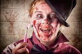 stock photo of gory  - Funny female zombie smiling with yellow rotting teeth at dentist holding toothbrush - JPG