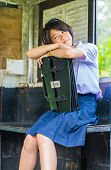 Cute Thai Shoolgirl Is Daydreaming In An Old Bus Stop