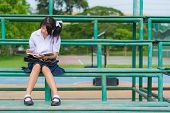 Cute Thai Schoolgirl Is Sitting And Reading On A Stand.cute Thai Schoolgirl Is Sitting And Reading O
