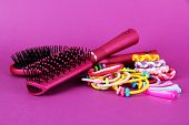 Scrunchies, hairbrush  and  hair - clip   on a pink background