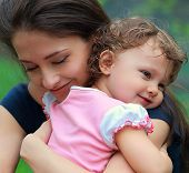 Happy Mother And Daughter Cuddling Outdoor Green Background