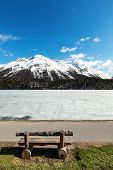 beautiful mountain landscape, lake frozen, wooden bench