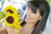 Pretty Italian Woman Looking at Sunflowers at the Street Market.
