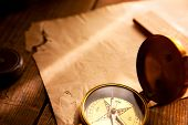 Old compass, old paper and a ray of light. Navigation and strategy.