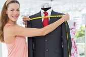 Portrait of a female fashion designer measuring suit on dummy at office