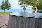 stock photo of infinity pool  - Feet of a girl sticking out of an infinity pool - JPG