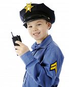 Closeup image of a happy young boy using his walkie talkie while in his police uniform.  On a white background.